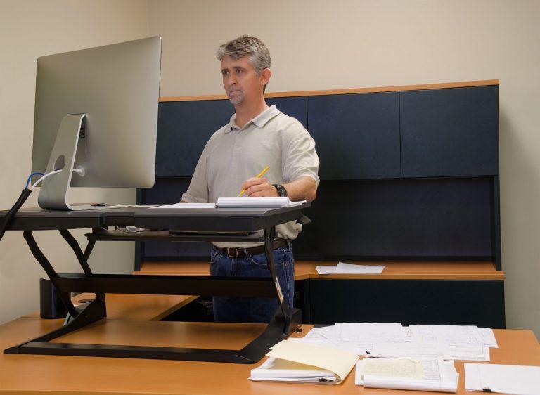 Ergonomic Assessments - man standing at desk using computer