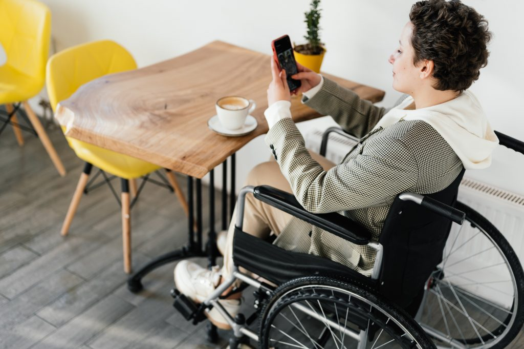 Occupational Therapist Sunshine Coast - woman in wheelchair at table using mobile phone